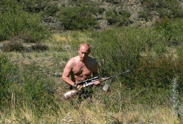 Vladimir Putin walks with a rifle in southern Siberia's Tuva region August 15, 2007. (Photo by Reuters/RIA Novosti/Kremlin)