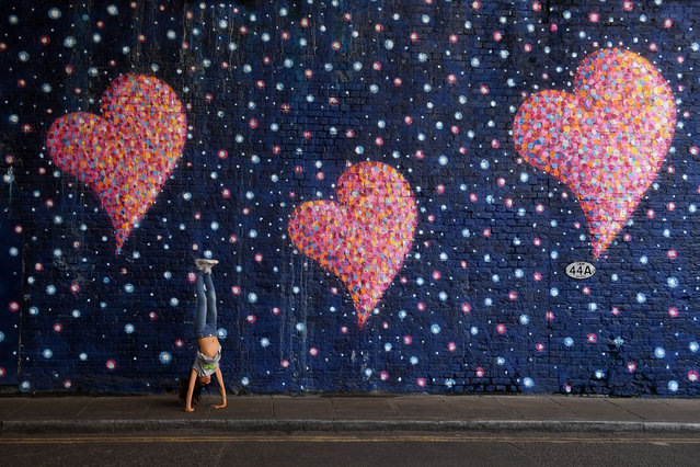 A young girl plays in front of a mural in a tunnel near Borough Market which was painted by graffiti artist James Cochran, also known as Jimmy C, and which commemorates the victims of the London Bridge terror attack on the first anniversary on June 3, 2018 in London, England. The anniversary will be marked by a service at Southwark Cathedral to honour the emergency services' response to last year's attack on 3 June, followed by a short procession from the cathedral to Southwark Needle, at the corner of London Bridge, ending with a minute's silence at 4.30pm. (Photo by Chris J. Ratcliffe/Getty Images)
