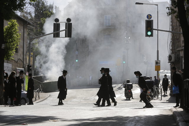 Men walk amid smoke from a dumpster fire, in an ultra-Orthodox neighborhood in Jerusalem, Sunday, January 24, 2021. Ultra-Orthodox demonstrators clashed with Israeli police officers dispatched to close schools in Jerusalem and Ashdod that had opened in violation of health regulations on Sunday. (Photo by Sebastian Scheiner/AP Photo)