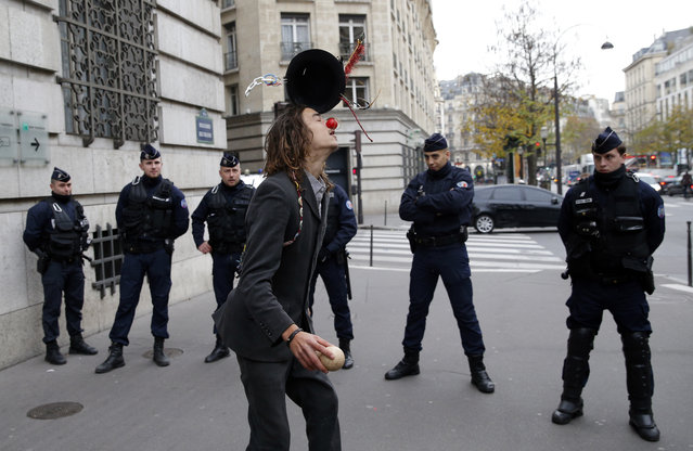"""An activist from the NGO """"Non violent action COP21"""" juggles with his hat in front of a bank to protest against tax evasion, in Paris, Thursday, December 3, 2015 . The protest is one of many activist actions linked to the COP21, the United Nations Climate Change Conference. (Photo by Christophe Ena/AP Photo)"""