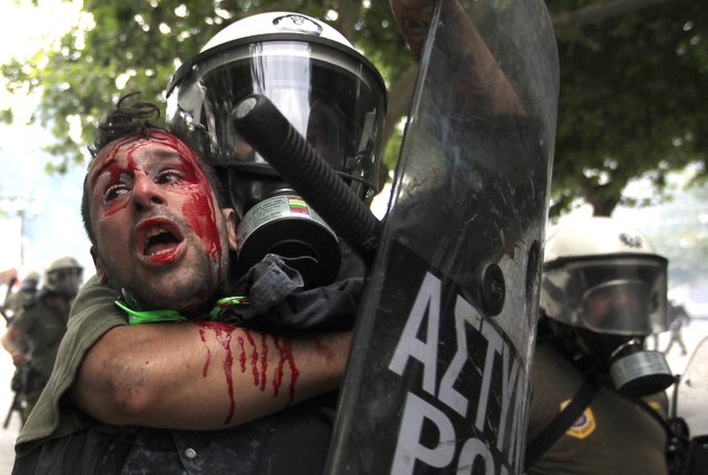 A demonstrator is detained by riot police during anti-austerity protests in Athens, in this June 29, 2011 file photo. (Photo by John Kolesidis/Reuters)