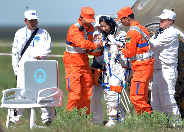 Chinese female astronaut Wang Yaping (3rd R) gets out of the Shenzhou-10 spacecraft that landed on the grasslands of north China's Inner Mongolia region on June 26, 2013, after a 15-day mission in space. China completed its longest manned space mission on June 26 as its Shenzhou-10 spacecraft and three crew members safely returned to Earth, in a major step towards Beijing's goal of building a permanent space station by 2020. (Photo by AFP Photo)