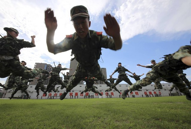 Paramilitary policemen jump as they practise during a summer drill in Hangzhou, Zhejiang province July 4, 2013. (Photo by Reuters/Stringer)