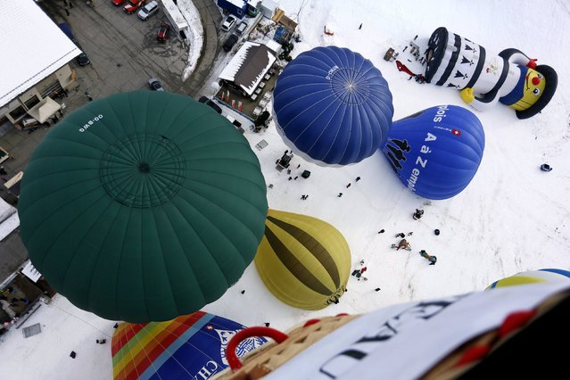 Balloons of all shapes and sizes get ready for take off at the 37th International Hot Air Balloon Week in Chateau-d'Oex, January 24, 2015. (Photo by Pierre Albouy/Reuters)