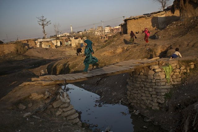 An Afghan refugee girl runs on a wooden bridge over a stream of rain water and sewage in a slum on the outskirts of Islamabad, Pakistan, Saturday, January 17, 2015. (Photo by Muhammed Muheisen/AP Photo)
