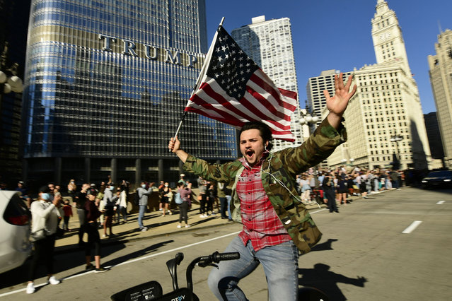 A supporter of President-elect Joe Biden celebrates while riding his bike outside Trump Tower Saturday, November 7, 2020, in Chicago. Democrat Joe Biden defeated President Donald Trump to become the 46th president of the United States on Saturday, positioning himself to lead a nation gripped by the historic pandemic and a confluence of economic and social turmoil. (Photo by Paul Beaty/AP Photo)