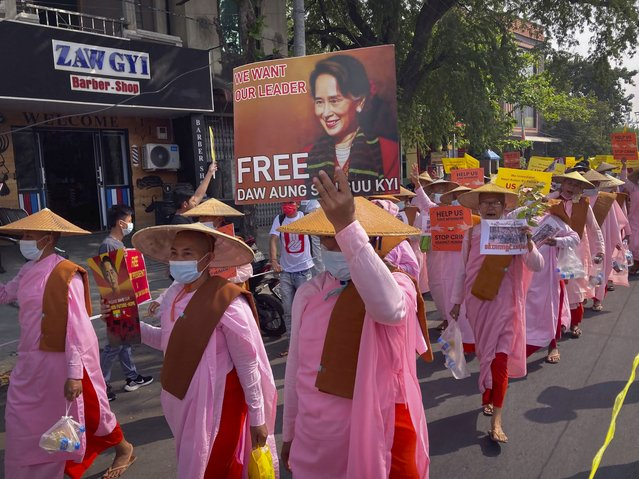 Buddhist nuns display images of deposed Myanmar leader Aung San Suu Kyi during a street march in Mandalay, Myanmar, Friday, February 26, 2021. Tensions escalated Thursday on the streets of Yangon, Myanmar's biggest city, as supporters of Myanmar's junta attacked people protesting the military government that took power in a coup, using slingshots, iron rods and knives to injure several of the demonstrators. (Photo by AP Photo/Stringer)