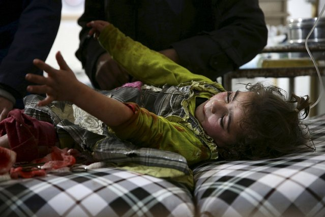 An injured girl reacts, after she was injured in what activists said was an airstrike by forces loyal to Syria's president Bashar al-Assad, inside a field hospital in the Douma neighborhood of Damascus, Syria December 5, 2015. (Photo by Bassam Khabieh/Reuters)