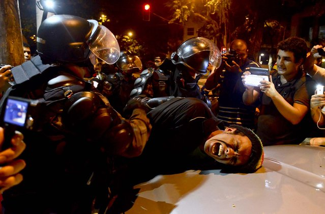 A demonstrator is detained by riot police during a protest against Rio de Janeiro governor Sergio Cabral, on July 18, 2013. Tens of thousands of Brazilians have taken to the streets since June in the biggest protests in 20 years, fueled by an array of grievances ranging from poor public services to the high cost of World Cup soccer stadiums and corruption. (Photo by Lucas Landau/Reuters)