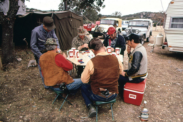 Deer hunters drink and play poker while waiting for deer. The hunters have built a permanent camp to which they return each year, November 1972. (Photo by Marc St. Gil/NARA via The Atlantic)