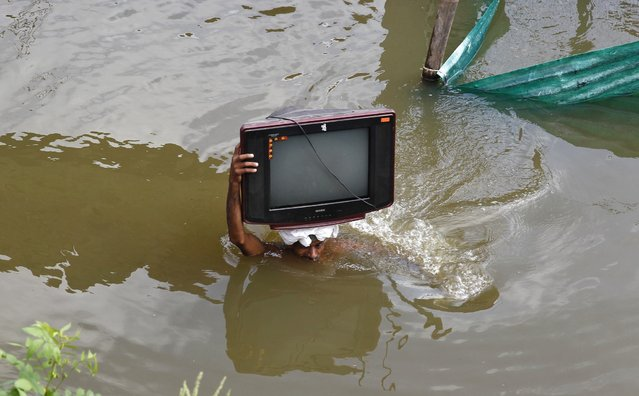 A flood-affected man carries his television set to a safer place, after heavy monsoon rains caused a rise in the water levels of the river Ganges, in the northern Indian city of Allahabad August 1, 2013. (Photo by Jitendra Prakash/Reuters)