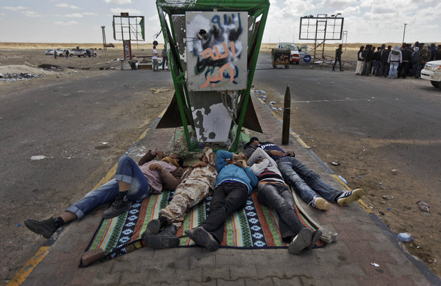 Weary Libyan rebels take a nap on the central reservation of the main road leading to the front line, on the outskirts of Ajdabiya, Libya Monday, April 18, 2011. (Photo by Ben Curtis/AP Photo)
