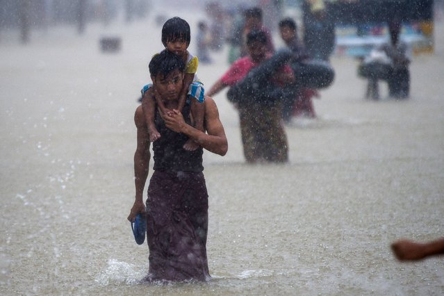A man carries a child through floodwaters in the Bago region, some 68 km away from Yangon, on July 29, 2018. Heavy monsoon rains have pounded Karen state, Mon state and Bago region in recent days and show no sign of abating, raising fears that the worst might be yet to come. (Photo by Ye Aung/AFP Photo)
