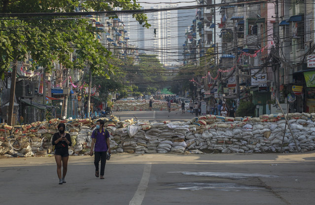 People walk along a deserted road blocked with improvised barricades build by anti-coup protesters to secure a neighborhood in Yangon, Myanmar, Thursday, March 18, 2021. (Photo by AP Photo/Stringer)