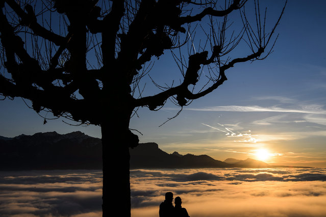 A couple watches the sunset over a sea of fog covering the Geneva Lake from Chardonne, Switzerland, 28 December 2015. (Photo by Jean-Christophe Bott/EPA)