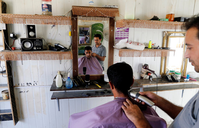 A Syrian refugee has a shave at a barber shop in Zaatari refugee camp near the border with Syria, in Mafraq, Jordan October 15, 2016. (Photo by Ammar Awad/Reuters)