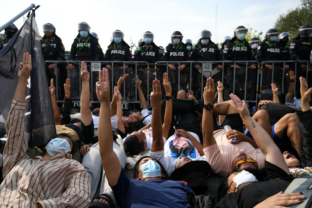 Protesters lie on the ground in front of riot police, showing three-finger salute, during a rally demanding release of arrested protest leaders and the abolition of Section 112 lese majeste law, outside the Government house in Bangkok, Thailand on March 30, 2021. (Photo by Chalinee Thirasupa/Reuters)
