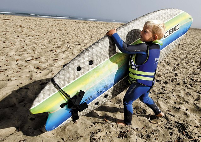 Triston carries his board. (Photo by Joe Johnston/The Tribune of San Luis Obispo)