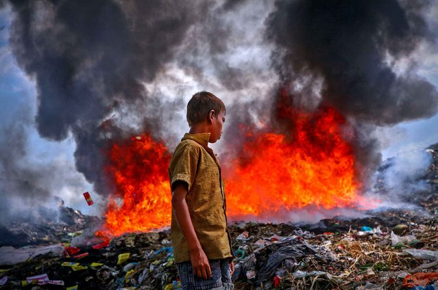 A boy looks for sellable materials close to the burning garbage in the permanent waste land under Sylhet City Corporation for a living, on January 15, 2015. (Photo by Md. Akhlas Uddin/Pacific Press)