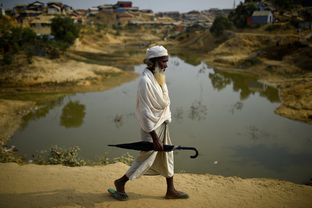 A Rohingya refugee walks with an umbrella at Jamtoli refugee camp in Cox's Bazaar, Bangladesh, March 31, 2018. (Photo by Clodagh Kilcoyne/Reuters)