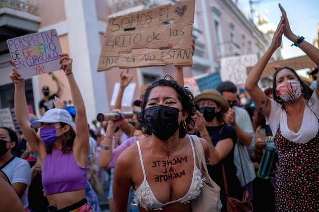 Protesting women shout slogans during a demonstration against sexual violence in front of the governor's mansion in San Juan, Puerto Rico on May 3, 2021. The demonstrators denounce the inaction and slowness of the state in implementing the executive order declaring a state of emergency against gender-based violence. (Photo by Ricardo Arduengo/AFP Photo)