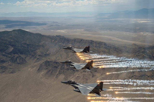 Three U.S. Air Force F-15E Strike Eagles,  from Mountain Home Air Force Base, Idaho, fire flares over the Utah Test and Training Range, west of Salt Lake CIty in Utah, U.S., July 3, 2018. (Photo by Airman 1st Class Codie Trimble/Reuters/U.S. Air Force)