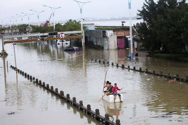 Residents paddle a makeshift raft as they make their way along a flooded street after Typhoon Fitow hit Rui'an, Zhejiang province October 7, 2013. Typhoon Fitow has affected the lives of 4.56 million people in east China's Zhejiang and Fujian provinces, the State Flood Control and Drought Relief Headquarters said on Monday, Xinhua News Agency reported. (Photo by Reuters/Stringer)
