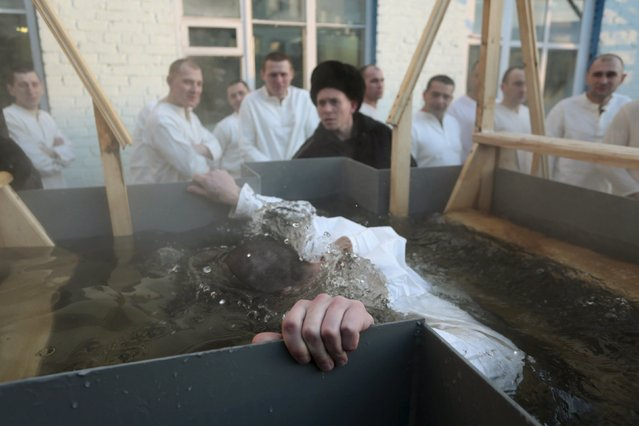 An inmate immerses himself in water at high-security penal colony number 6 during celebrations for the Orthodox Epiphany, with the air temperature at about minus 29 degrees Celsius (minus 20.2 degrees Fahrenheit), in the Siberian city of Omsk, Russia, January 18, 2016. Orthodox believers mark Epiphany on January 19 by immersing themselves in icy waters regardless of the weather. (Photo by Dmitry Feoktistov/Reuters)