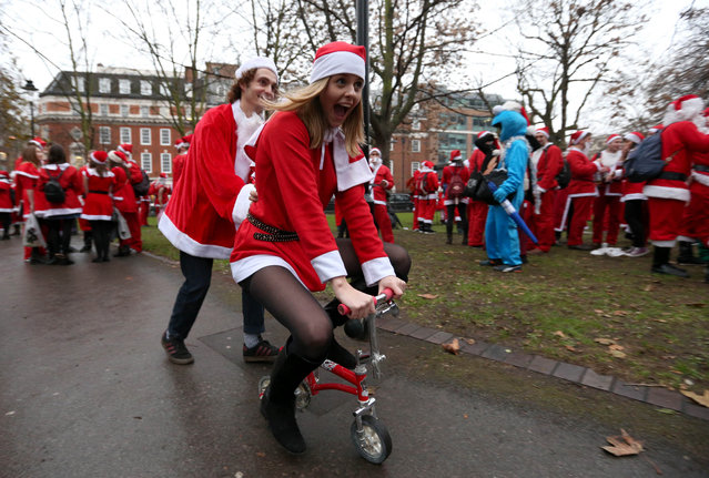 A woman rides a mini bicycle through crowds of Santa costumes in a park during the annual SantaCon on December 10, 2016 in London, England. The event sees hundreds of people walking the streets of London and drinking alcohol in Father Christmas and other festive costumes. (Photo by PA Wire)