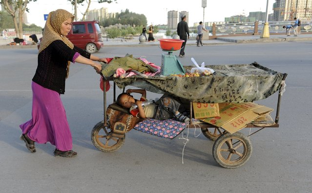 An ethnic Uighur woman pushes her fruit stall while her child lies in it along a street in Asku, Xinjiang Uighur Autonomous Region in this June 14, 2012 file photo. (Photo by Reuters/Stringer)
