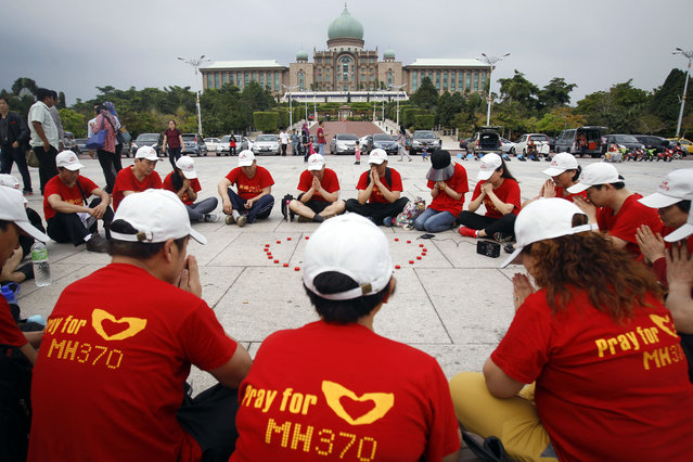Unidentified Chinese family members of passengers on board the missing Malaysia Airlines flight MH370 pray outside the prime minister's office in Putrajaya, Malaysia on Wednesday, Feb. 18, 2015.  Flight 370, which disappeared last March 8 while flying from Kuala Lumpur to Beijing, is believed to have crashed in the southern Indian Ocean, off western Australia. (AP Photo/Joshua Paul)