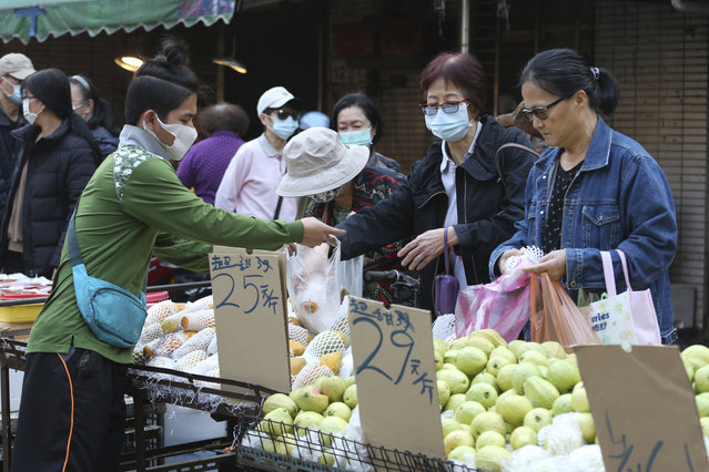 People wear face masks to help curb the spread of the coronavirus as they shop at a market in Taipei, Taiwan, Monday, January 25, 2021. (Photo by Chiang Ying-ying/AP Photo)