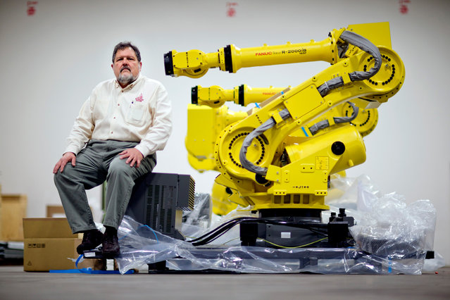 Rosser Pryor, Co-owner and President of Factory Automation Systems, sits next to a new high-performance industrial robot at the company's Atlanta facility, on January 15, 2013. Pryor, who cut 40 of 100 workers since the recession, says while the company is making more money now and could hire ten people, it is holding back in favor of investing in automation and software. (Photo by David Goldman/AP Photo)
