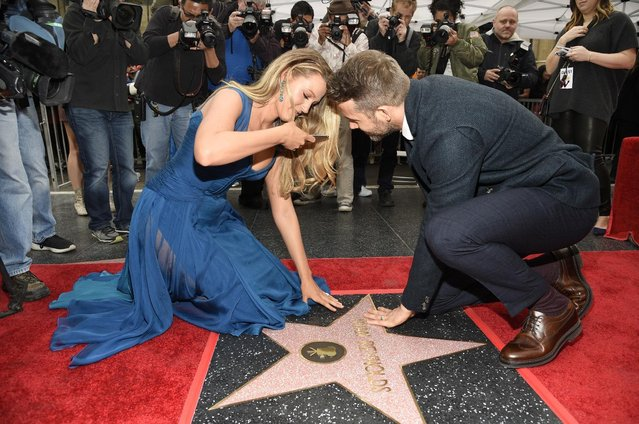 Actor Ryan Reynolds, right, joins his wife, actress Blake Lively, as she photographs his new star on the Hollywood Walk of Fame following a ceremony on Thursday, December 15, 2016, in Los Angeles. (Photo by Chris Pizzello/Invision/AP Photo)