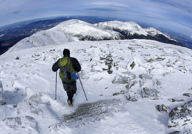 In this Tuesday, March 10, 2015 photo, a hiker leaves the summit of Mount Washington, New Hampshire.  The snow-covered peaks of the northern presidential range can be seen in the distance. They are, from left, Mounts Clay, Jefferson, Adams and Madison. (Photo by Robert F. Bukaty/AP Photo)