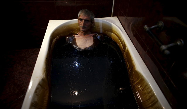 AZERBAIJAN: A man lies in a bathtub filled with crude oil during a health therapy session at Naftalan Health Center in Baku, Azerbaijan June 27, 2015. According to Hashim Hashimov, a medical specialist at the center, the oil can heal more than seventy diseases, including neurological diseases, skin conditions and impotence. Centres like Naftalan attract people coming from Russia, Kazakhstan and Germany, Hashimov told Reuters. (Photo by Stoyan Nenov/Reuters)