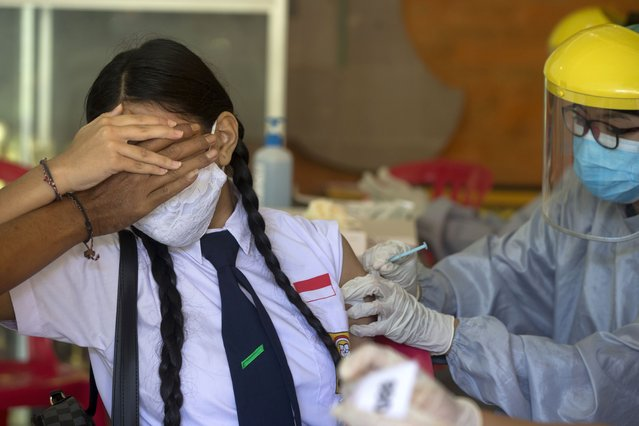 A teenager reacts as she receives a shot of the Sinovac vaccine for COVID-19 during a vaccination campaign at a school in Denpasar, Bali, Indonesia on Monday, July 5, 2021. (Photo by Firdia Lisnawati/AP Photo)