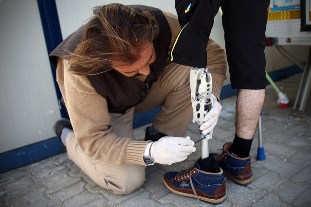 Abdulaziz Bastin (L), a prosthetics technician from Belgium, adjusts a new leg given to Omar Hawt who lost his left leg in a barrel bomb attack on Aleppo in Syria at a temporary border hospital on March 23, 2015 in Reyhanli, Turkey. Turkey has one of the largest populations of Syrian refugees fleeing the ongoing civil war with official estimates currently at 1.6 million. (Photo by Carl Court/Getty Images)