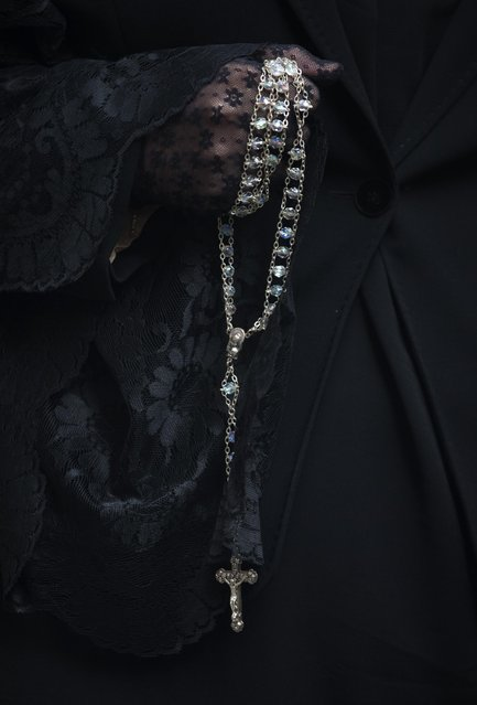 A penitent from the La Borriquita brotherhood holds a crucifix during a Palm Sunday Holy week procession in Madrid, Spain, Sunday, March 29, 2015. (Photo by Paul White/AP Photo)