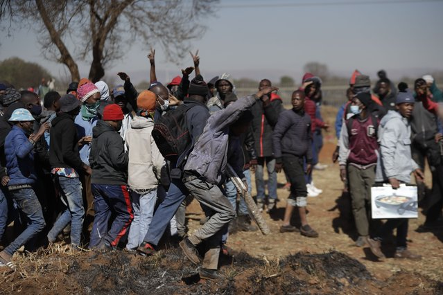 A group of men shout as they try to enter a shopping mall in Vosloorus, east of Johannesburg, South Africa, Wednesday July 14, 2021. South Africa's rioting continued Wednesday as police and the military struggle to quell the violence in Gauteng and KwaZulu-Natal provinces. The violence started in various parts of KwaZulu-Natal last week when Zuma began serving a 15-month sentence for contempt of court. (Photo by Themba Hadebe/AP Photo)