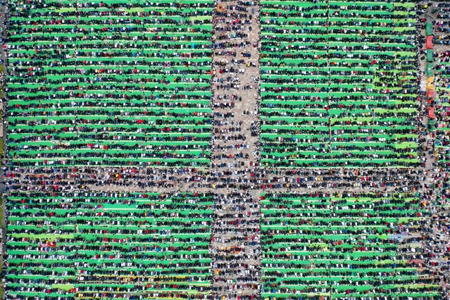 This aerial photo taken on May 13, 2021, shows Albanian Muslims praying at Skenderbej square on the first day of the Muslim festival marking the end of the holy fasting month of Ramadan in Tirana. - Muslims celebrate the Eid Al-Fitr holiday, which marks the end of the fasting month of Ramadan. (Photo by Gent Shkullaku/AFP Photo)