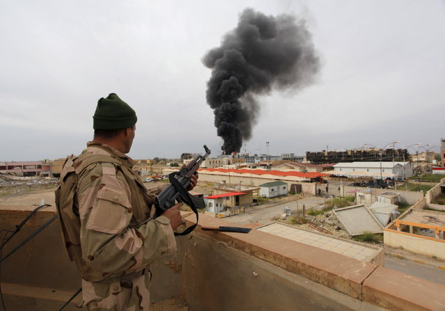 A member from the Iraqi security forces looks at smoke rising in Tikrit April 1, 2015. (Photo by Alaa Al-Marjani/Reuters)