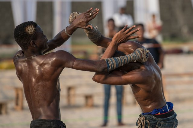 Two young Dambe boxers fight during the Dambe Warriors Tournament held in Lagos on March 2, 2018. Dambe, a brutal style of fighting where one wrapped fist is a designated spear and the other a shield, is traditionally practised by Hausas in Nigeria's north, but on this night the fight was in the southern city of Lagos. The attempt to introduce Dambe to the megacity's elite was notable less for the fighting than as a showcase of Nigeria's complexity. (Photo by Stefan Heunis/AFP Photo)