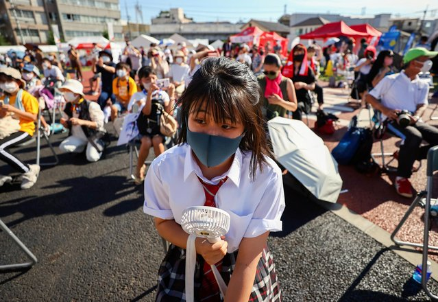 A family member of a torch relay runner wearing a protective mask uses a portable electric fan to cool down as she attends a torch kiss event during Tokyo 2020 Olympic torch relay celebration at Shinagawa Central Park in Tokyo, Japan, July 21, 2021. (Photo by Issei Kato/Reuters)