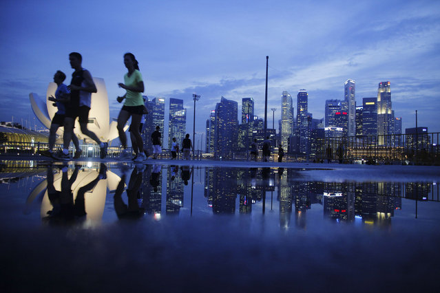 Joggers run pass as the skyline of Singapore's financial district is seen in the background April 21, 2014. (Photo by Edgar Su/Reuters)