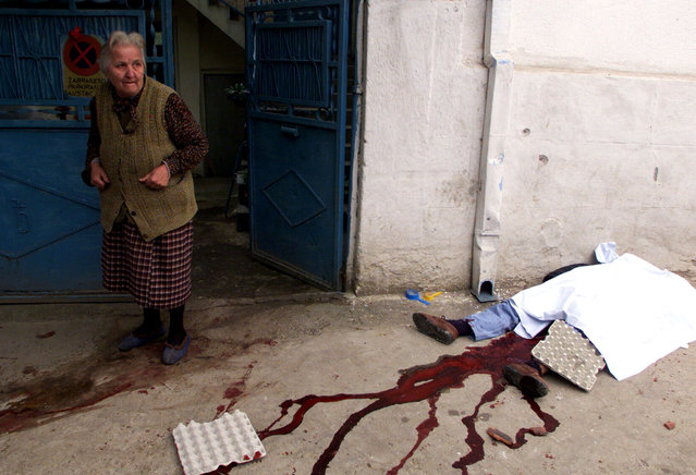 A woman stands near a dead man after a NATO daylight air raid near a market over the town of Nis, south of Belgrade, May 1999. (Photo by Desmond Boylan/Reuters)