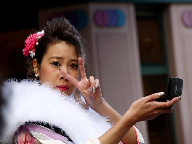 A Japanese woman wearing a kimono makes a V sign while she checks her make-up during the Coming of Age Day celebration in Tokyo, Japan January 9, 2017. (Photo by Kim Kyung-Hoon/Reuters)