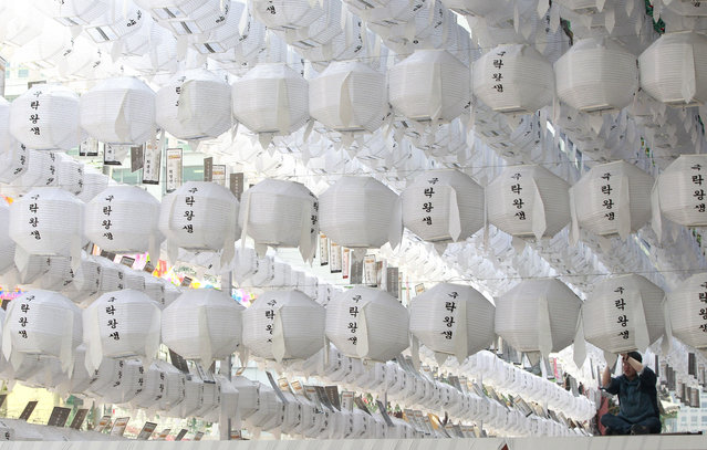 "A worker attaches the name tag of a Buddhist who made a donation to a lantern for the upcoming celebrations for Buddha's birthday on May 25 at Jogye Temple in Seoul, South Korea, Thursday, April 9, 2015. The letters on lanterns read: ""A gentle and easy death"". (Photo by Ahn Young-joon/AP Photo)"