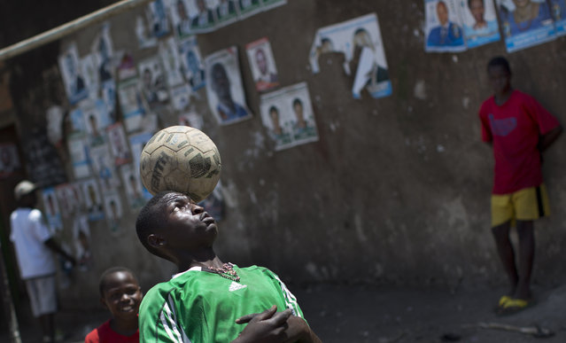 A boy practices balancing tricks in front of a wall plastered with campaign posters for opposition leader Kizza Besigye, as well as for local members of Parliament, in a poor market area of the capital Kampala, Uganda Wednesday, February 17, 2016. (Photo by Ben Curtis/AP Photo)