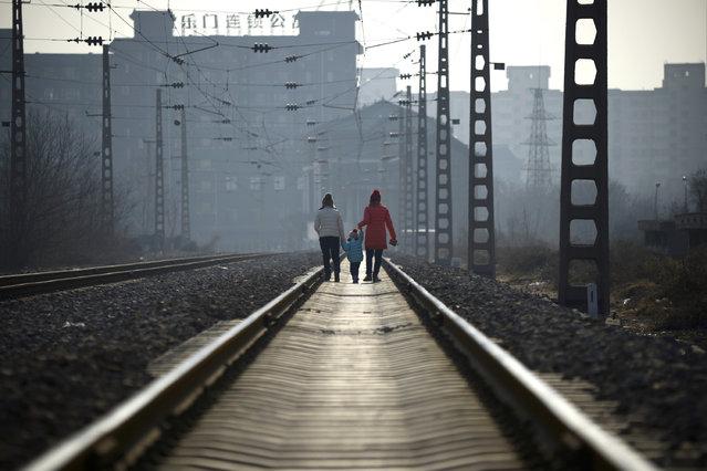 Two women carrying a child walk along a railway in Beijing on January 12, 2017. (Photo by Wang Zhao/AFP Photo)